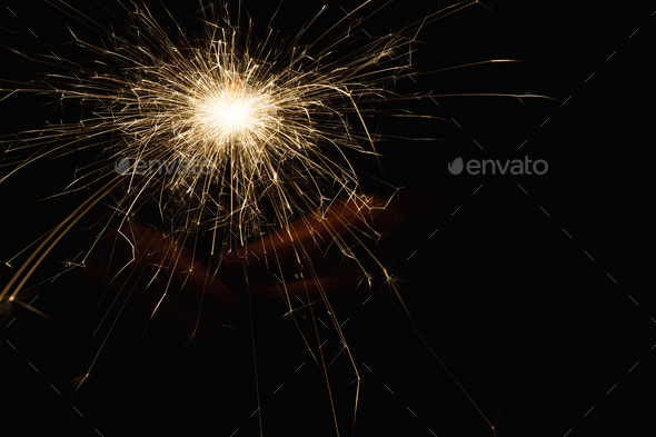 New year party sparkler in female hands on black background - Stock Photo - Images