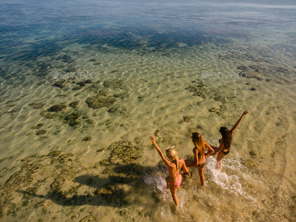 Young women running into the sea - Stock Photo - Images
