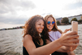 Female friends taking selfie with mobile phone by the lake