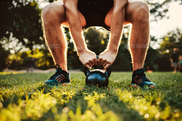 Man doing kettlebell workout in the park - Stock Photo - Images