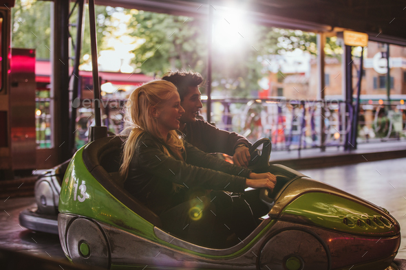 Happy young couple driving a bumper car at amusement park - Stock Photo - Images
