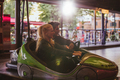 Happy young couple driving a bumper car at amusement park - PhotoDune Item for Sale