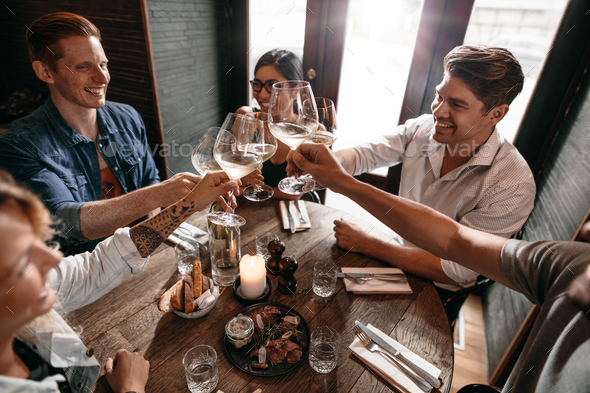 Young friends toasting wine at cafe - Stock Photo - Images