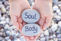 Woman holding stone with the words Soul and Body in her palms - PhotoDune Item for Sale