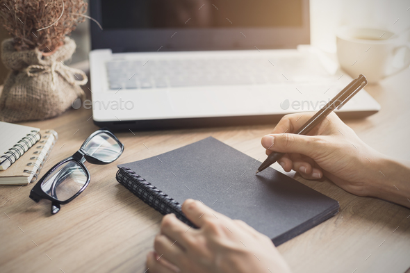 woman writing on notebook at workplace - Stock Photo - Images