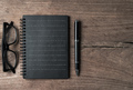 Black notebook on old wooden background
