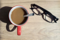 Cup of coffee and glasses with shadow on wooden desk