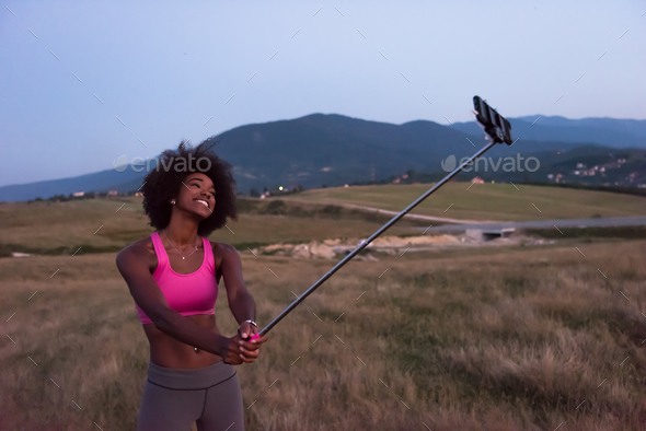 black woman photographing herself in nature - Stock Photo - Images