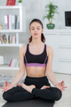 fit woman meditating in lotus pose in the living room