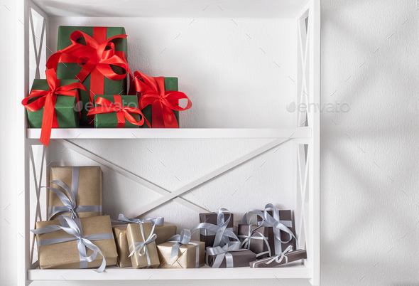 Holiday presents, gift boxes on white shelves at wall background - Stock Photo - Images