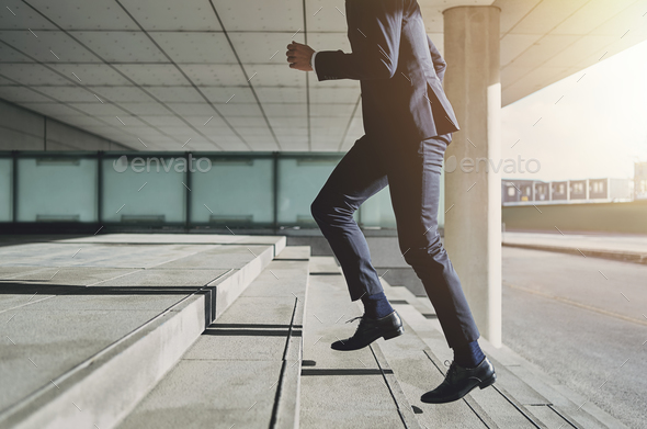Man wearing suit runs up the stairs - Stock Photo - Images