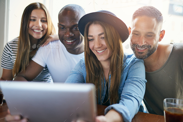 Woman holding tablet and showing to friends - Stock Photo - Images