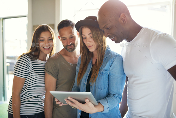 Four adults interested with something on tablet - Stock Photo - Images