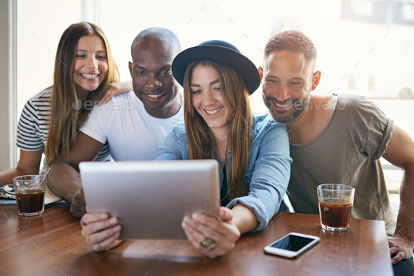 Woman sharing something on tablet with friends - Stock Photo - Images