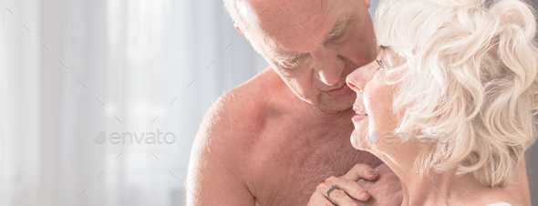 Elderly naked man embracing his wife - Stock Photo - Images