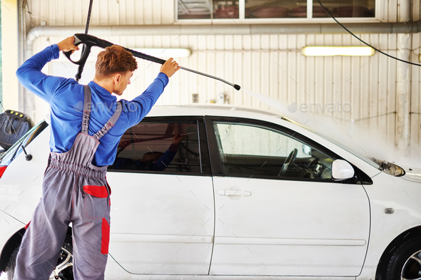 Man worker washing car on a car wash - Stock Photo - Images