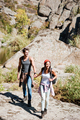 Smiling couple walking with backpacks over mountains