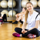 Confident Woman Sitting Cross Legged In Fitness Center - PhotoDune Item for Sale