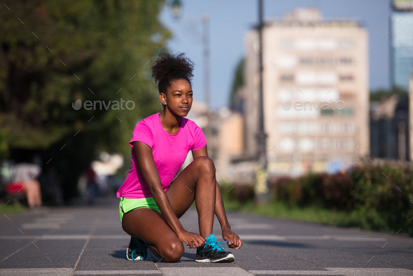 African american woman runner tightening shoe lace - Stock Photo - Images
