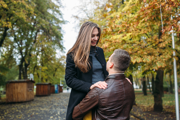 attractive happy couple walking in autumn park - Stock Photo - Images