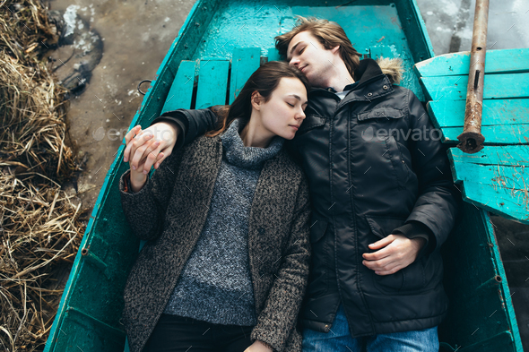 man and woman lie in the boat - Stock Photo - Images