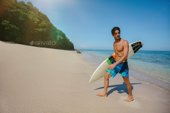 Male surfer holding surf board walking out of the sea - Stock Photo - Images