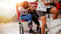 Teenage girls sitting on tricycle using mobile phone - PhotoDune Item for Sale