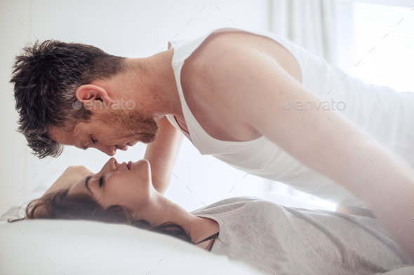 Intimate young couple during foreplay in bed - Stock Photo - Images