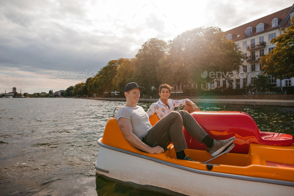 Teenage boys boating on the lake in city - Stock Photo - Images
