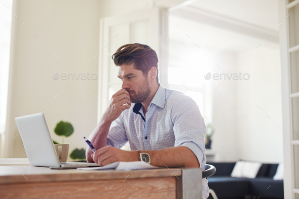 Pensive young man working on laptop at home - Stock Photo - Images