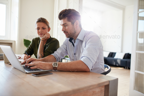 Young man working on laptop with woman sitting by - Stock Photo - Images