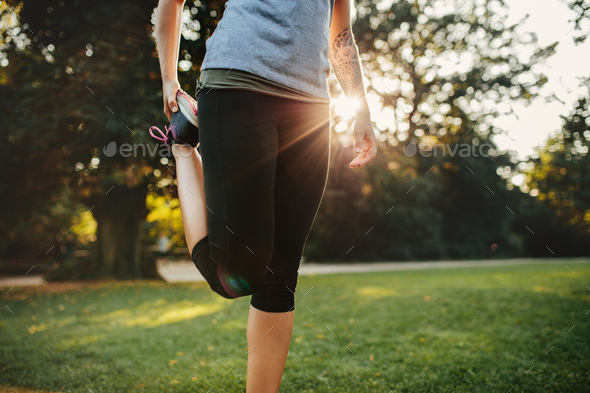 Fitness woman stretching legs in park - Stock Photo - Images