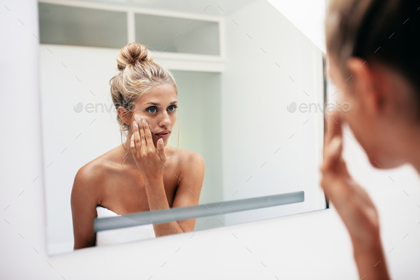 Female putting on moisturizer on her facial skin - Stock Photo - Images