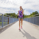 Focused young woman running on bridge over a lake - PhotoDune Item for Sale