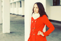 Fashion beautiful young woman wearing a red coat jacket and scar