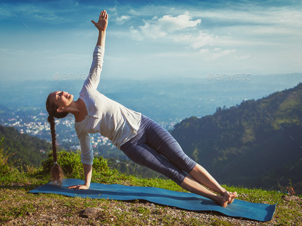 Woman doing yoga asana Vasisthasana - side plank pose outdoors - Stock Photo - Images