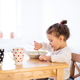 Little girl sitting at the table, eating breakfast - PhotoDune Item for Sale