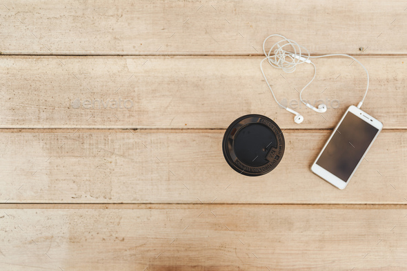 Phone with headphones and coffee on wood blank space