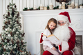 Santa Claus and child at home. Christmas gift. Family holiday concept - PhotoDune Item for Sale
