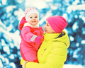 Winter portrait happy smiling mother holds baby on her hands ove