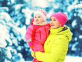 Winter portrait happy mother holds baby on hands over snowy chri