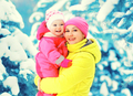 Winter portrait happy smiling mother holds baby on hands over sn