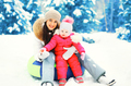 Winter happy smiling mother and child sitting on sled in snowy d