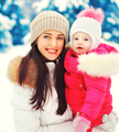 Winter portrait happy smiling mother and baby on hands over snow