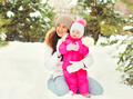 Winter portrait happy smiling mother with child over snowy chris