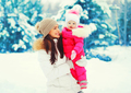 Winter portrait happy smiling mother with baby on her hands over