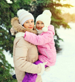 Winter happy mother and child over christmas tree and snowflakes
