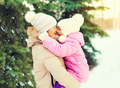 Winter happy mother hugging child over christmas tree and snowfl