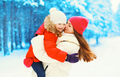Winter happy smiling mother hugging kissing child over snowflake