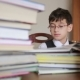 Boy Sitting at a Table with a Stack of Books. Child Reading. Boy with Glasses - VideoHive Item for Sale